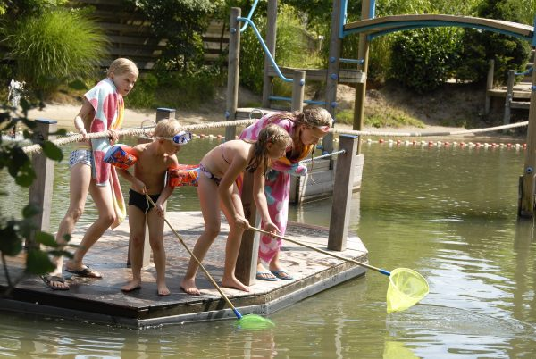 Kinder spielen am Badesee mit einander
